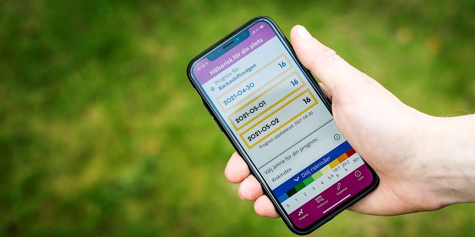 En hand håller i en smartphone med appen Luft Stockholm synlig på skärmen.